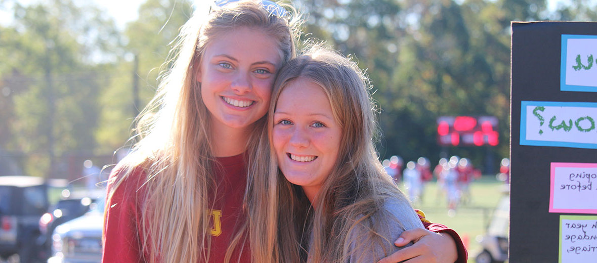Two students smiling at camera outside