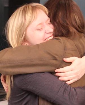 Two females hugging, one visible and smiling.