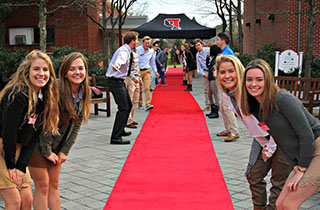 A welcoming red carpet surrounded by students smiling