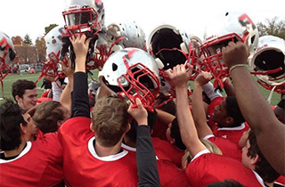 Football players holding their helmets 至gether in a huddle.