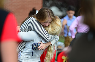 Two alumnae hugging and smiling.