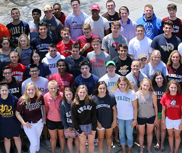 Large Group of seniors wearing college sweatshirts smiling.