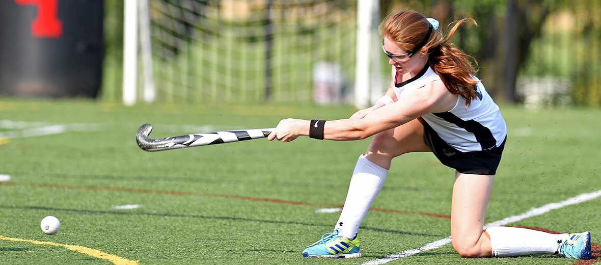 Field hockey player hitting ball.