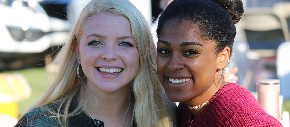 Two female students smiling at camera.