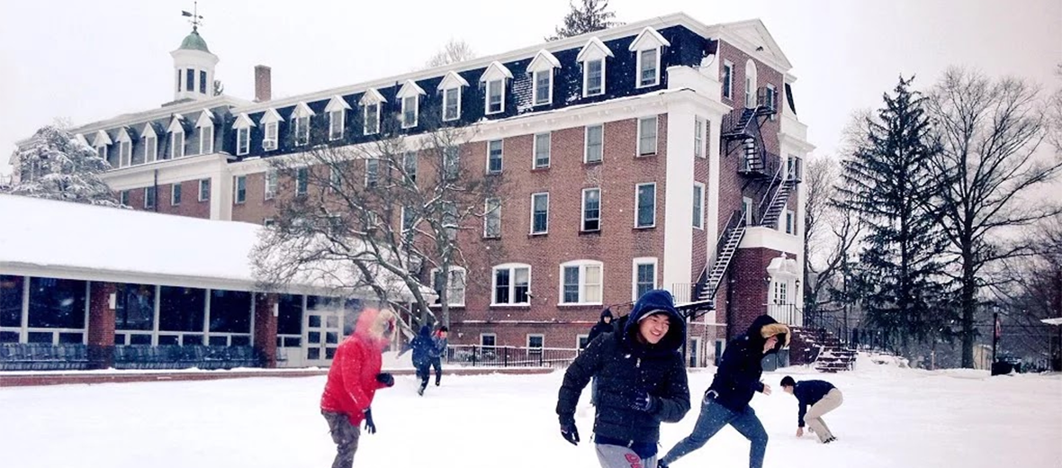 Old Main, campus in snow with students playing outside